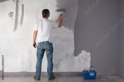Man painting a wall.