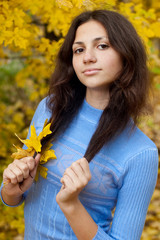Beautiful young girl is by an autumn day with yellow maple leave