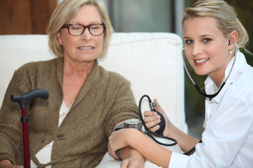 A doctor taking her patient blood pressure.