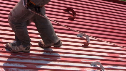 Worker walks on a roof with safety line