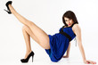 Sexy lady in blue dress sitting on a floor.