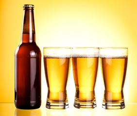 Three glasses and Bottle of fresh light beer
