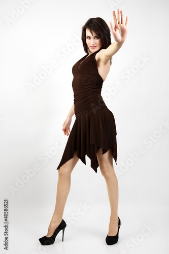 Young woman in brown dress making stop gesture.
