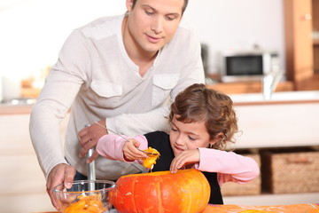 Father with daughter emptying pumpkin