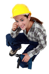 A female construction worker with a drill.