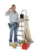 Carpenter stood with equipment making telephoning customer