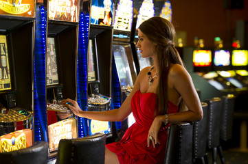 Young woman playing with slot machines