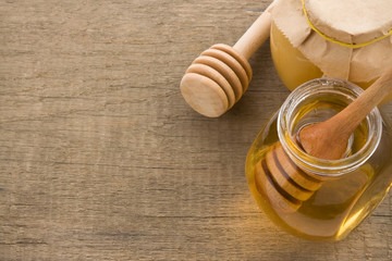 jar and pot of honey with stick on wood