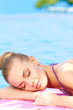 Woman sleeping next to swimming pool