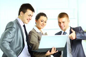 Young businesswoman with her collegues using laptop