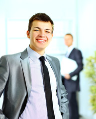 young man in a business suit. In an office