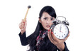 Angry businesswoman ready to hit an alarm clock