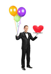 Butler holding a tray with a red heart shape on it and balloons