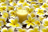 Yellow candles and frangipani flower on bamboo mat