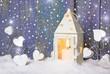 Weiße Laterne mit Herzen im Schnee