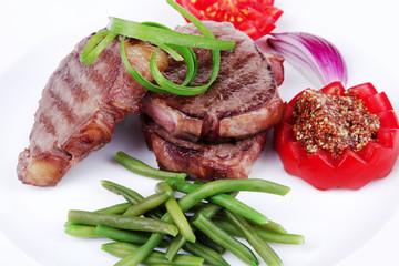 beef steaks strips on white plate