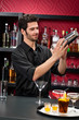 Young bartender make cocktail shaking drinks