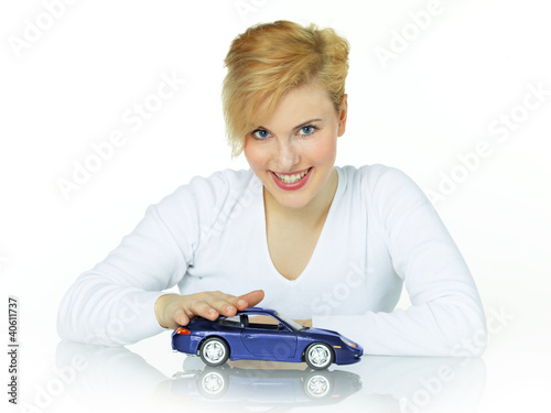 Pretty girl strokes her dream car on white background