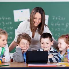 schüler und lehrerin schauen auf laptop
