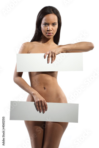 Very beautiful nude model is holding a board in her hands on whi