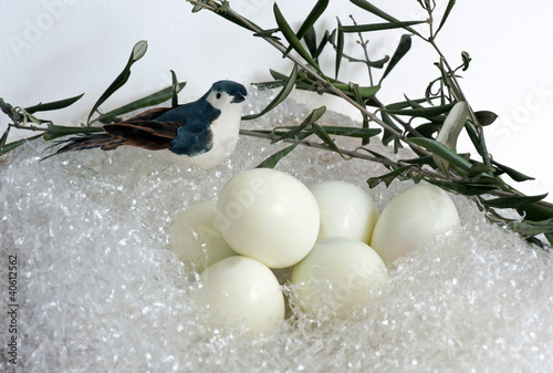 Easter: boiled eggs in a nest with fabric bird and olive branch
