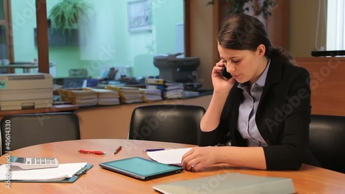 Young businesswoman talking on the phone in office