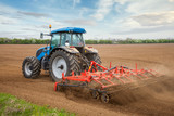 Small scale farming with tractor and plow in field - 40615317