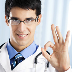 Smiling doctor with okay gesture, at office