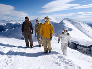 Snowboarders walking along ridge of  mountains