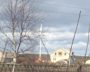 fast spinning windmill  houses and spring tree with buds. speed