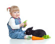 Funny little girl feeding a rabbit with carrot and lettuce on th