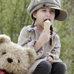 Kind mit Zöpfen schleckt ein Eis