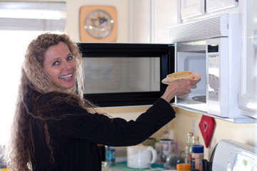 woman puts food in oven