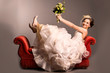 Portrait of a beautiful happy bride on red sofa
