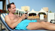 Young man sending sms while sunbathing by the pool