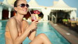 Woman sitting by swimming pool and drinking exotic cocktail