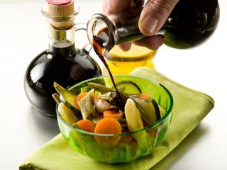 pouring balsamic vinegar over steamed vegetables salad