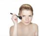 portrait einer jungen schönen blonden Frau beim schminken freig
