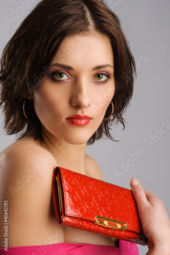 Young beautiful woman with a red purse