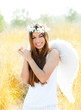 Angel girl in golden field with feather white wings