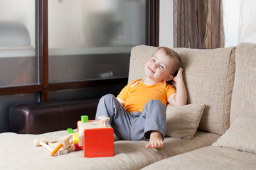adorable boy siiting with wooden building toys at home
