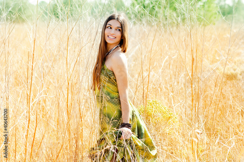 Asian indian woman walking outdoors in golden field