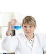 female chemist mixing liquids in test tubes