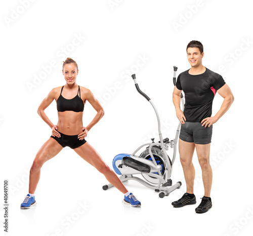 Female and male athletes posing next to a cross trainer machine