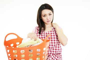 洗濯物を持った肩こりに悩む女性