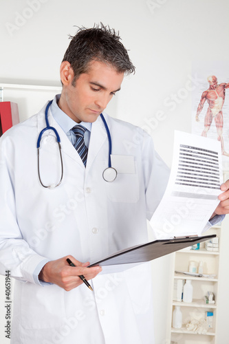 Male Doctor Looking at Clipboard