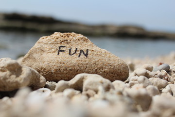 The word FUN written on a rock at the beach