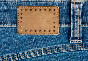 Blank leather jeans label decorated by rivets