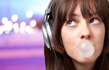 portrait of young woman listening to music with bubble gum over