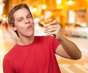 portrait of young man eating pizza portion at night city